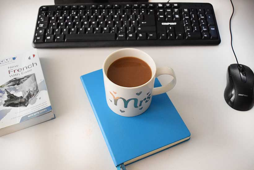 a cup of coffee with a french language book and computer equipment