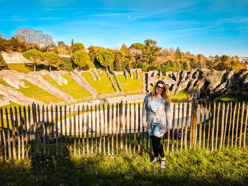 gallo-roman-ampitheatre-in-saintes-france-and-brie-anne-stood-infront-of-the-fence-to-it-for-the-what-to-do-in-saintes-france-blog-post