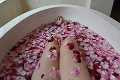brie-anne in a bath tub covered in roses during her balinese holiday